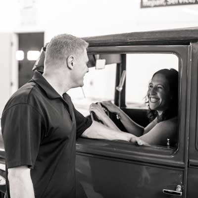 man talking to woman in classic car - black and white