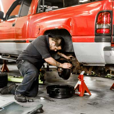man working on a trucks brakes
